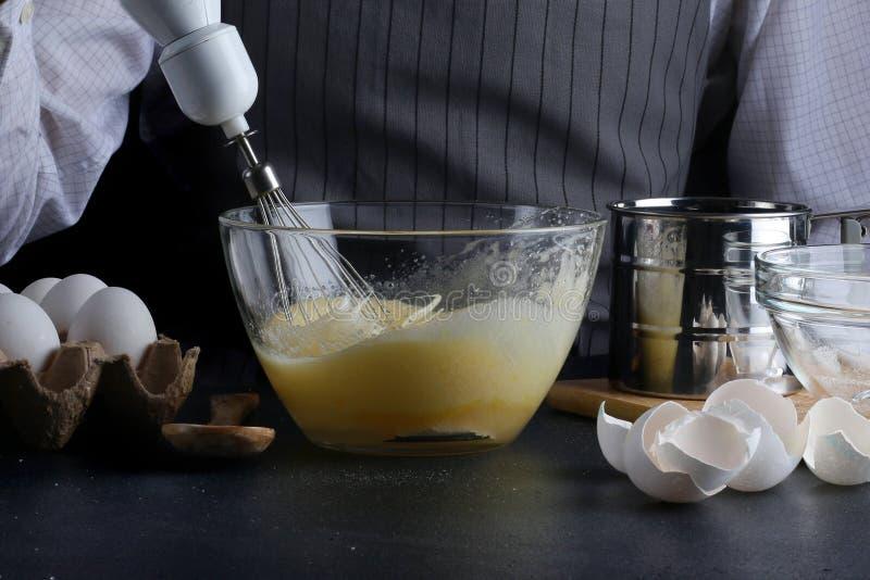 Teig, der aus dem Schneebesen ausläuft manking Torte des Mannes Rezeptkonzept auf dunklem Hintergrund lizenzfreie stockbilder