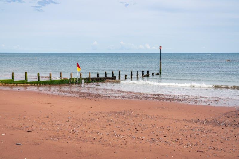 Teignmouth Beach, Devon, England. A groyne and a flag on the beach in Teignmouth, Devon, England, UK royalty free stock photo