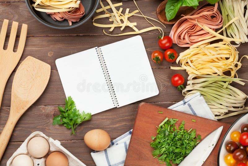 Teigwaren, die Bestandteile und Geräte auf Holztisch kochen stockfoto