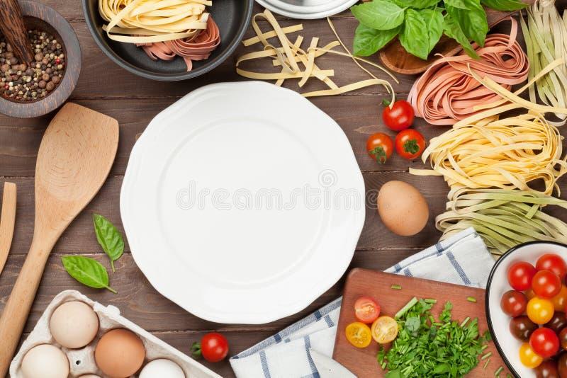 Teigwaren, die Bestandteile und Geräte auf Holztisch kochen lizenzfreies stockfoto
