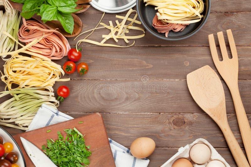 Teigwaren, die Bestandteile und Geräte auf Holztisch kochen stockbilder