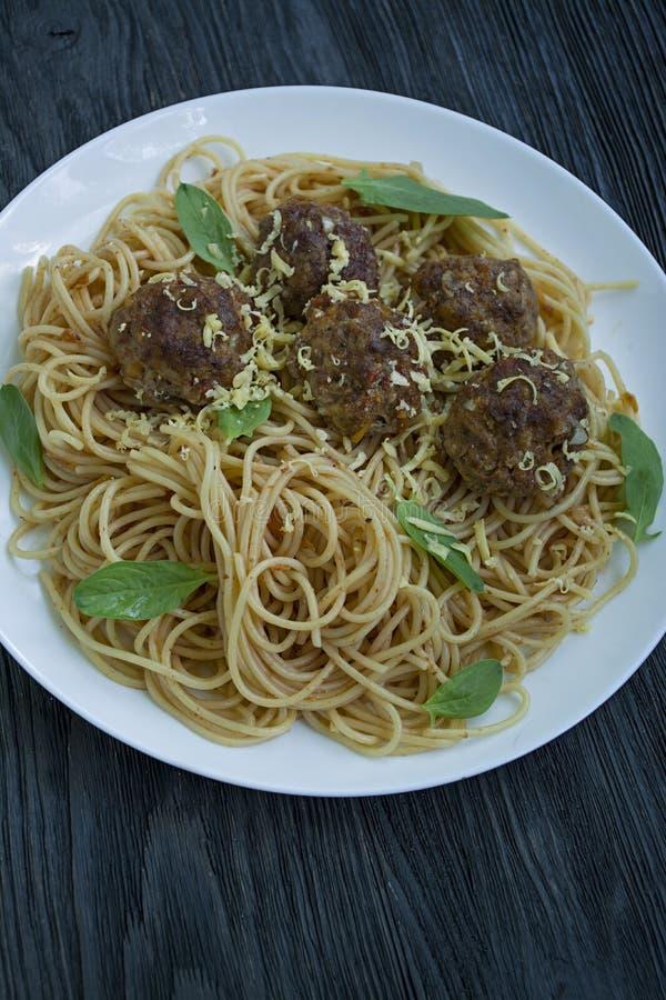 Teigwaren mit Fleischklöschen und Petersilie in der Tomatensauce Dunkler h?lzerner Hintergrund Ansicht von oben stockfotos
