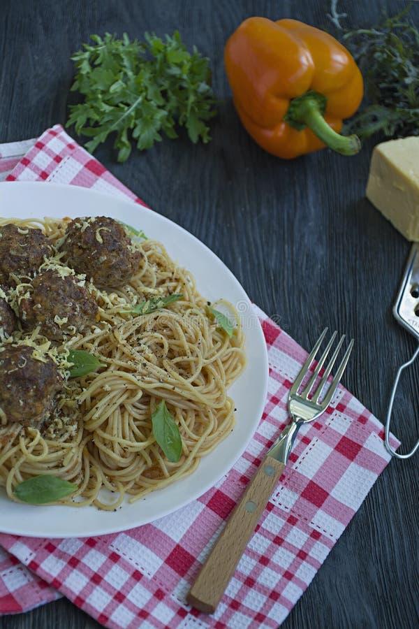 Teigwaren mit Fleischklöschen und Petersilie in der Tomatensauce Dunkler h?lzerner Hintergrund Ansicht von oben lizenzfreies stockfoto