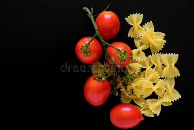 Teigwaren mit Kirschtomaten auf einem schwarzen Hintergrund lizenzfreies stockfoto