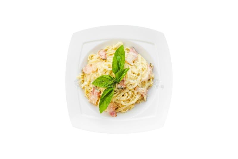 Teigwaren mit Speck, Creme, Basilikum, Parmesankäse, Knoblauch, Eigelb auf weißer Platte Isolationsschlauch getrennt auf weißem H stockfotos