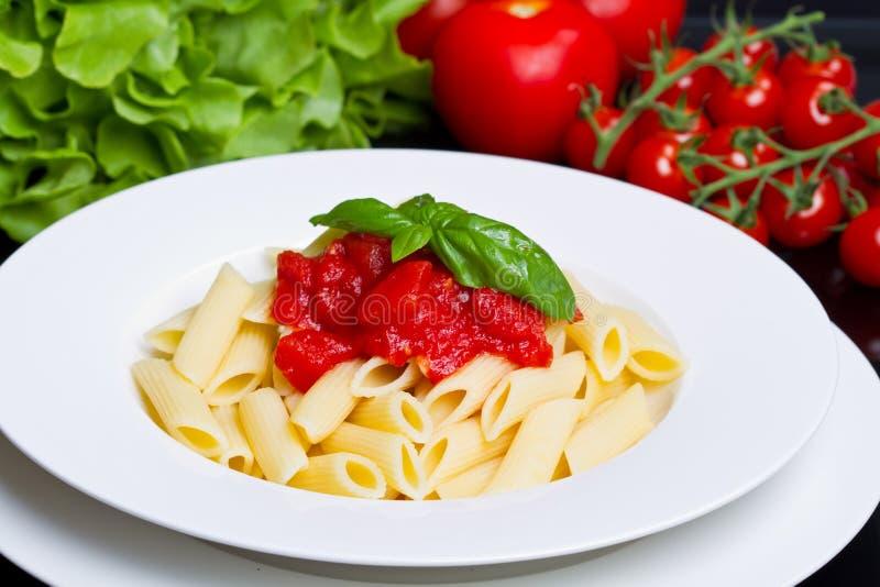 Teigwaren mit Tomatensauce und Basilikum lizenzfreie stockfotografie