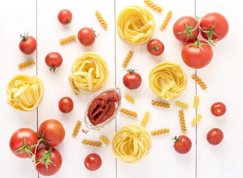 Teigwaren-Produkte mit Tomaten-rohes Teigwaren Fusili-Fettuccine-Bestandteil-italienisches Lebensmittel-weißer Hintergrund-Draufs lizenzfreie stockfotos