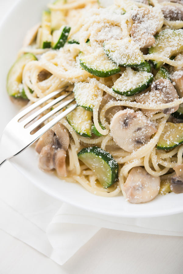 Teigwaren (Spaghettis) mit Zucchini, Pilzen, sahniger Soße und Parmesankäse lizenzfreie stockfotografie