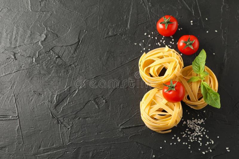 Teigwaren, Tomaten und Salz auf schwarzem Hintergrund stockfotos