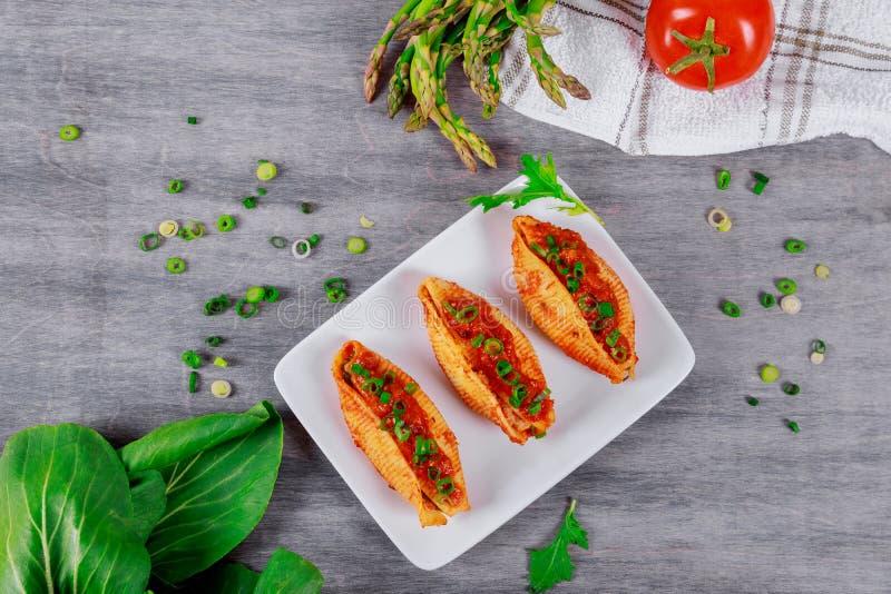 Teigwarenoberteile angefüllt mit gehacktem Rindfleischfleisch mit Kräutern und Tomatensauce stockbild