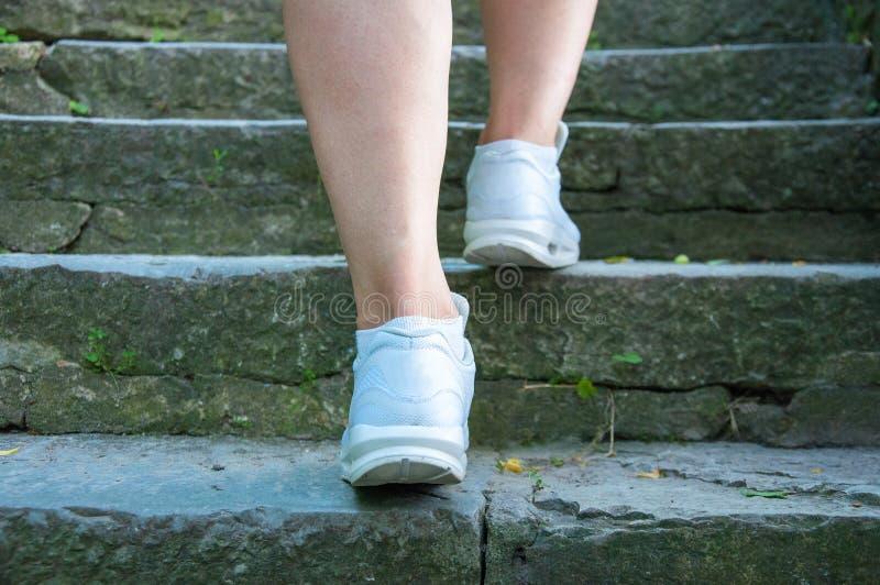 Teil der Beine einer Frau in den weißen Turnschuhen gehend entlang Steinschritte lizenzfreies stockbild