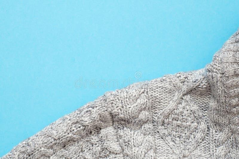 Teil der grauen gestrickten Strickjacke auf blauem Hintergrund lizenzfreies stockbild