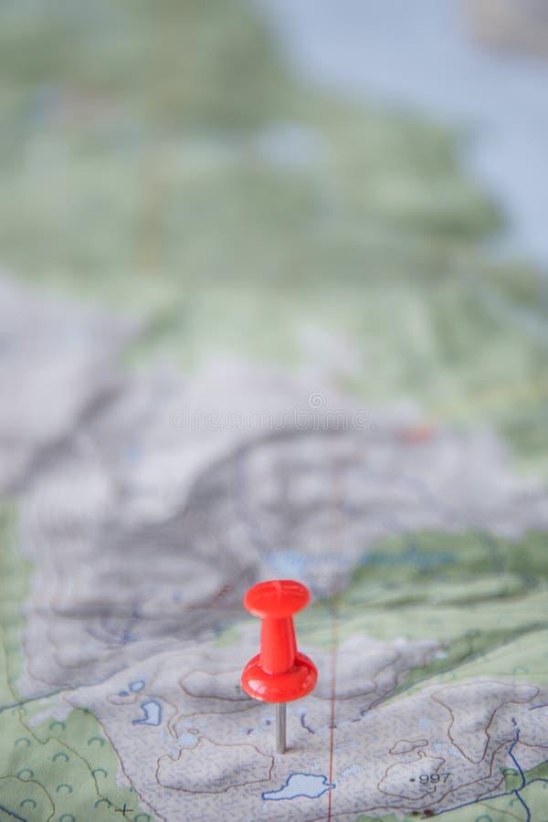 Teil der Welttopo-Karte als entscheidendes Einzelteil für erfolgreiche Reise und roten Stoßstift als Standortmarkierung, Zusammen stockfotografie