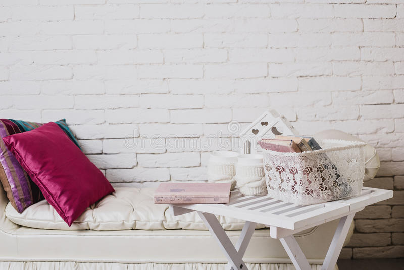 Teil des Innenraums mit Couch und dekorativen Kissen, weißer Holztisch mit Büchern auf ihr stockbilder