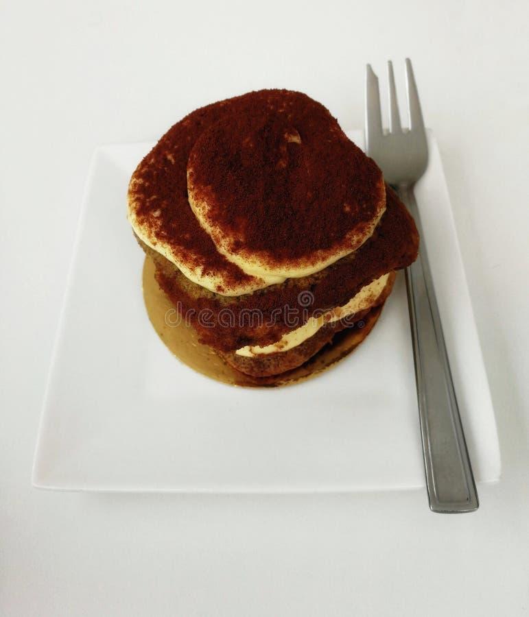 Teil des Tiramisukuchens in einem weißen quadratischen Teller stockfotografie