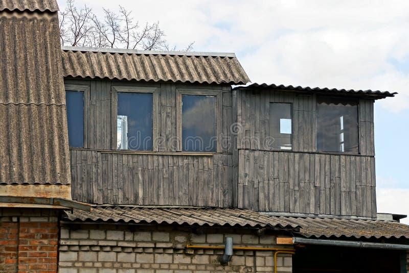 Teil eines alten Hauses mit einem grauen hölzernen Dachboden und Fenstern stockfotografie