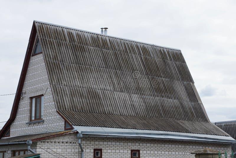 Teil eines Backsteinhauses mit einem Fenster im Dachboden unter einem grauen Schieferdach stockbild