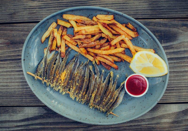 Teil frische geschmackvolle Fische mit Pommes-Frites auf Holztisch lizenzfreie stockbilder