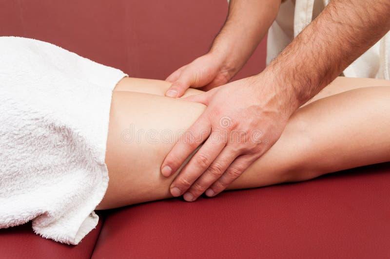 Teil weibliche Beine, die eine Massage durch männlichen Masseur erhalten stockbilder