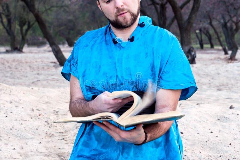 Teilansicht des starken hübschen bärtigen Mannes im blauen Kimono, der durch großes Buch Blätter treibt lizenzfreie stockfotografie
