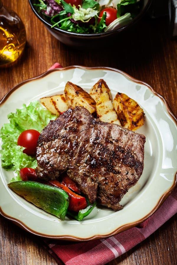 Teile gegrilltes Rindfleischsteak mit gegrillten Kartoffeln und Paprika lizenzfreies stockbild