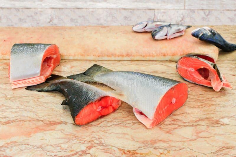 Teile gehackte Lachsfische auf Marmortabelle stockbild