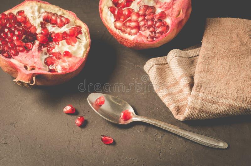 Teile Granatapfel und Löffel/Teile des Granatapfels und ein Löffel auf einem dunklen Hintergrund, Abschluss oben lizenzfreies stockbild
