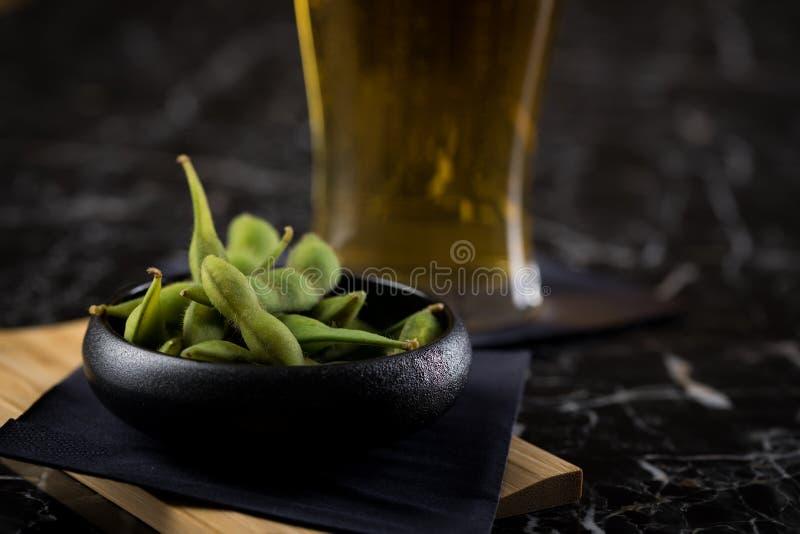 Teilen Sie japanische Edamame-Sojabohnenölbohnen in der Porzellanschüssel auf hölzernem Brett mit Bierglas auf Serviette und schw lizenzfreie stockfotos
