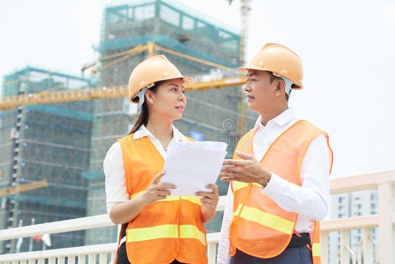 Teilhaber, die Bauvorhaben besprechen lizenzfreies stockbild