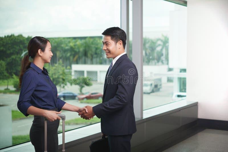 Teilhaber, die im Flughafen sich treffen lizenzfreies stockbild