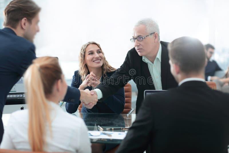 Teilhaber rütteln Hände im Konferenzsaal lizenzfreie stockfotos