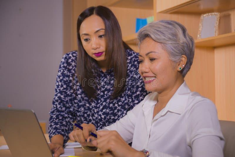 Teilhaberfrauen, die glücklich und erfolgreich am Bürolaptopcomputertisch in den weiblichen Kollegen des Jobs zusammenarbeiten un stockfotografie