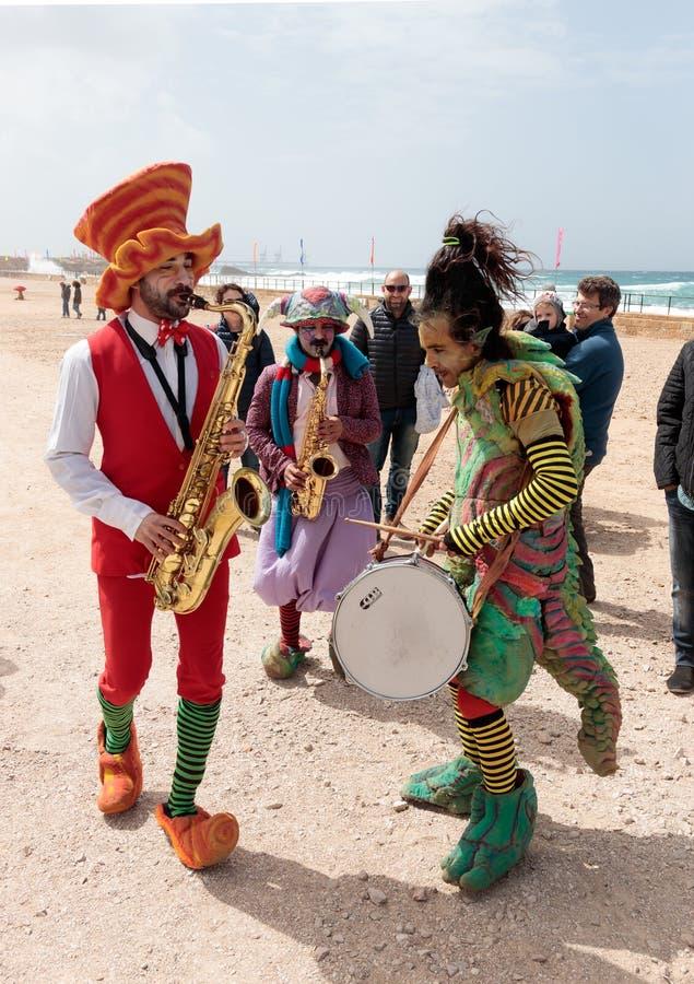 Teilnehmer des Festivals gekleidet als Clowne, die musikalisches instr spielen stockbilder
