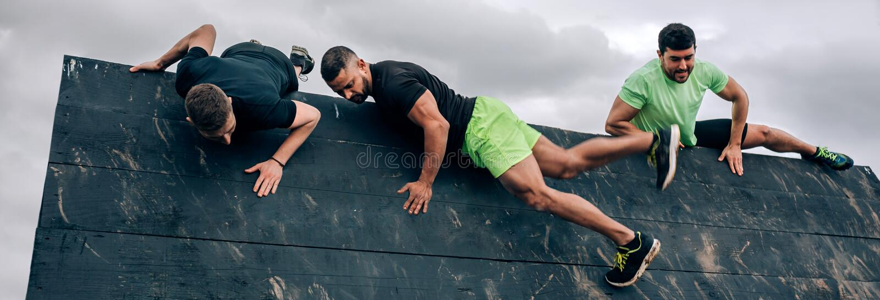 Teilnehmer an Hindernislaufkletterwand lizenzfreies stockbild