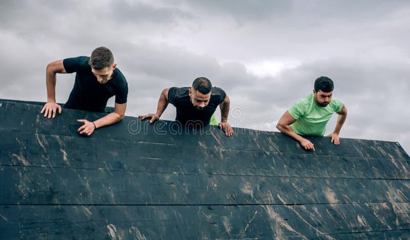 Teilnehmer an Hindernislaufkletterwand stockfotografie
