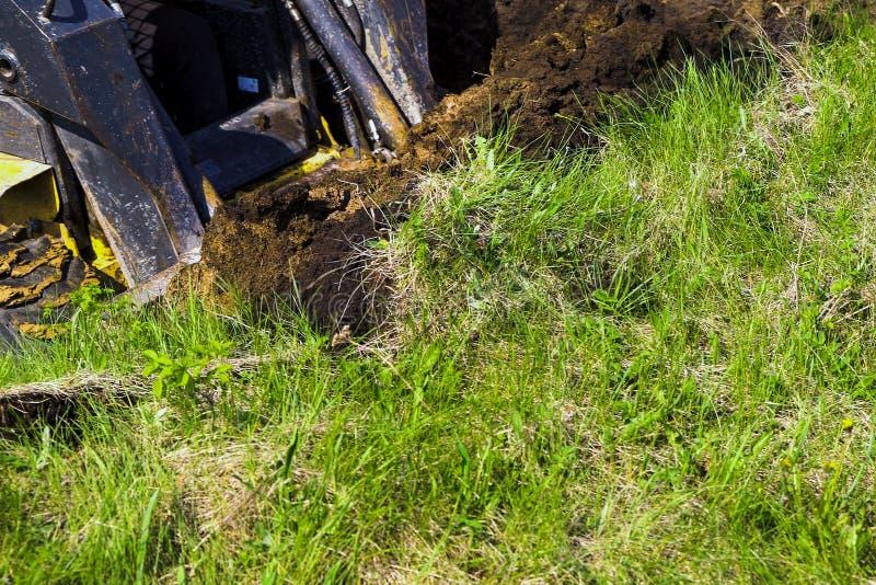 Teilweise Ansicht der grabenden Grube des Baggereimers im grasartigen Boden während der Erdarbeiten lizenzfreie stockbilder