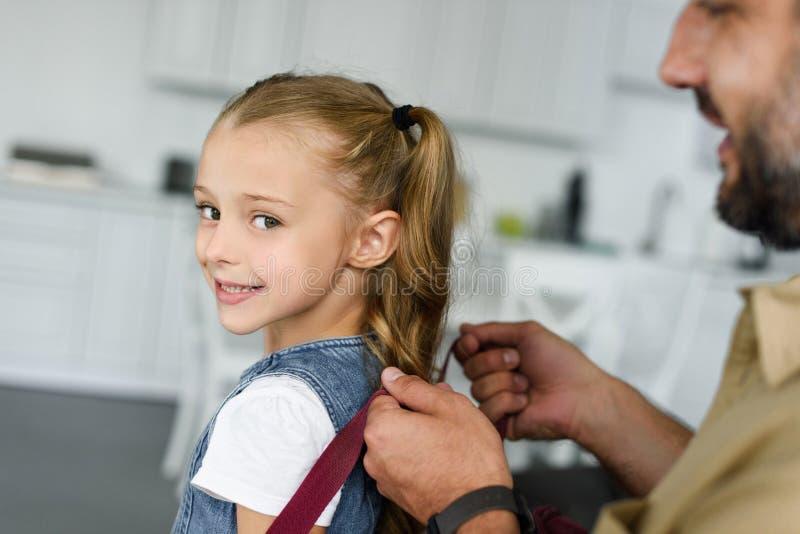 teilweise Ansicht der helfenden Tochter des Vaters, zum des Rucksacks zurück zu zu Hause zu tragen lizenzfreies stockfoto
