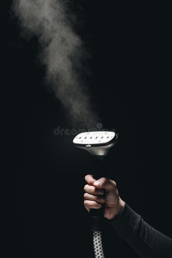 teilweise Ansicht der Nahaufnahme der Person Kleiderdampfer mit Dampf halten lizenzfreie stockbilder
