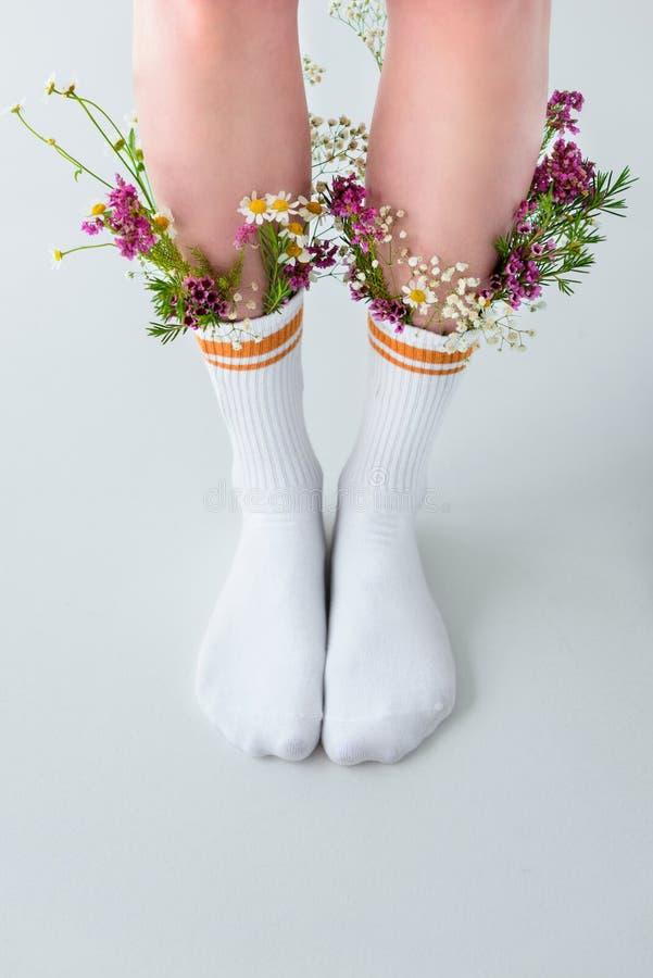 teilweise Ansicht der Nahaufnahme von weiblichen Beinen in den Socken mit schönen Blumen stockfoto