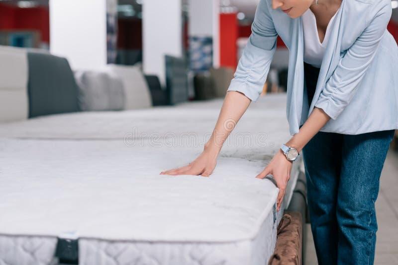 teilweise Ansicht der rührenden orthopädischen Matratze der Frau stockbilder