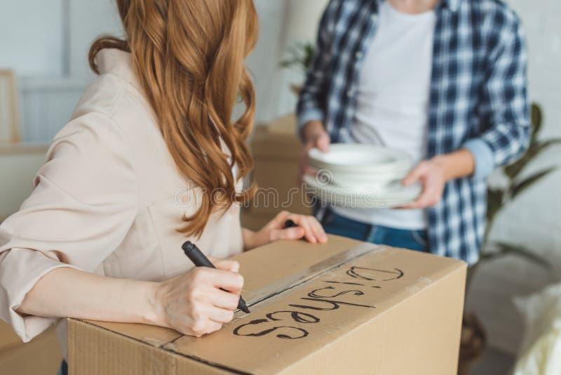 teilweise Ansicht der unterzeichnenden Pappschachtel der Frau mit Ehemann mit Tellern nahe vorbei, bewegend stockfotos