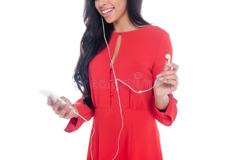 teilweise Ansicht des Afroamerikanermädchens in rotes Kleiderhörender Musik in den Kopfhörern mit dem Smartphone lokalisiert stockbild