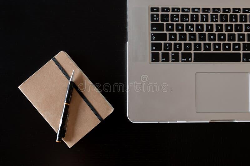 Teilweise Ansicht einer silbernen Tastatur eines Laptops und des Notizbuches mit einem Bleistift auf einem dunklen hölzernen Schr lizenzfreie stockfotografie