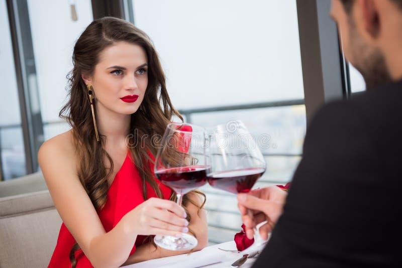 teilweise Ansicht von klirrenden Gläsern der Paare Rotwein während des romantischen Datums lizenzfreie stockfotografie