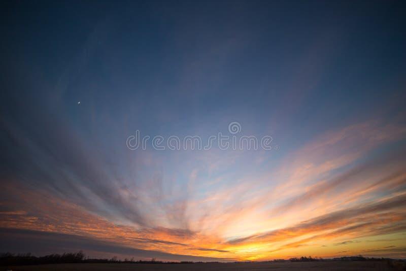 Teilweise bewölkter drastischer Sonnenuntergang-Himmel über Winter-Feldern und Met lizenzfreie stockfotos