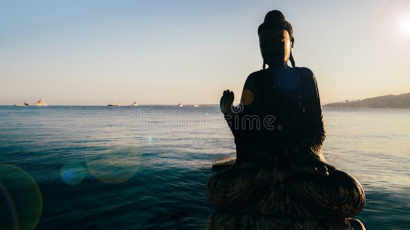 Teilweises Schattenbild von hölzernem Buddha im Wasser stockfotografie