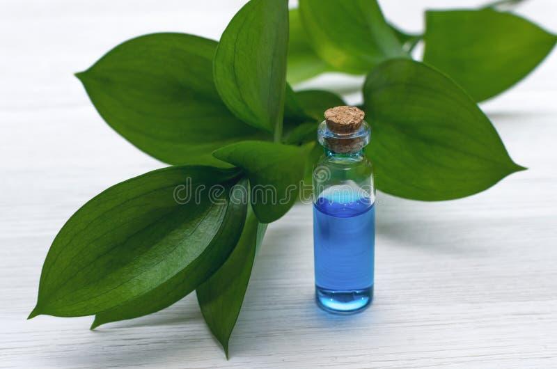 Teinture bleue d'huile d'essence sur le fond en bois blanc image libre de droits