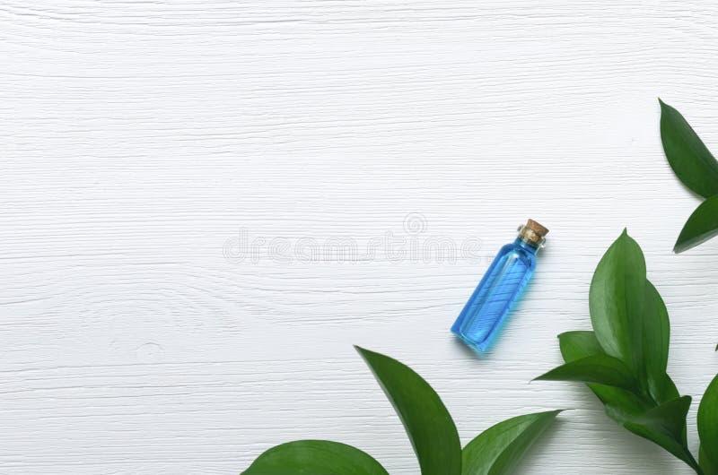 Teinture bleue d'huile d'essence sur le fond en bois blanc images libres de droits