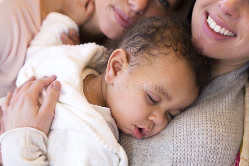 Tej samej płci para snuggling ich syna zdjęcia stock