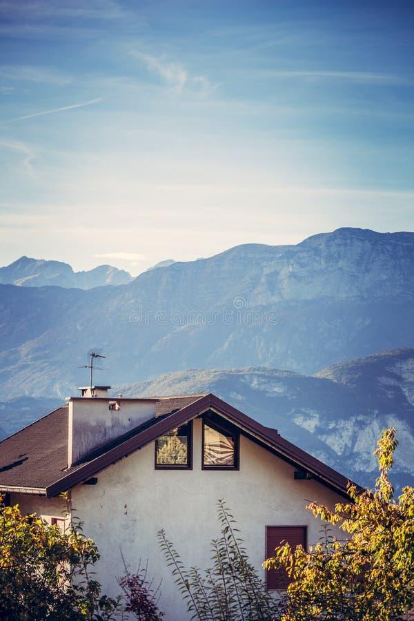Tejado alpino de la casa contra las montañas imagen de archivo libre de regalías